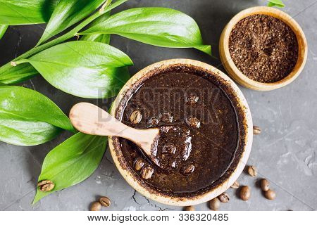 Coffee Scrub In A Wooden Bowl With A Wooden Spoon On A Dark Stone Background. Nearby Is A Bowl With
