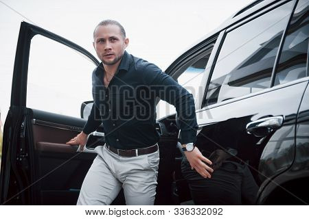 Portrait Of A Young Bodyguard Near The Car. He Performs Dangerous Work.