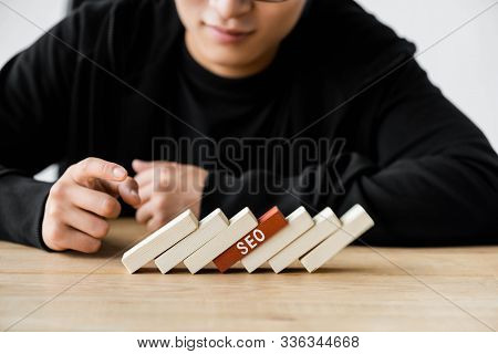 Cropped View Of Seo Manager Pointing With Finger At Wooden Rectangles With Lettering Seo