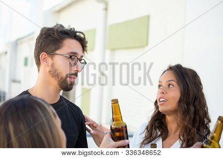 Group Of Friends Discussing News Over Bottle Of Beer On Outdoor Terrace. Young Men And Women In Casu
