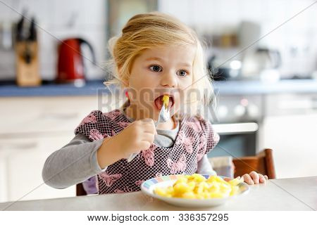 Lovely Toddler Girl Eating Healthy Fried Potatoes For Lunch. Cute Happy Baby Child In Colorful Cloth