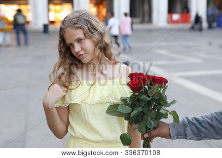 Young Girl Refuses Flowers From A Street Seller.  European Girl With Blue Eyes And Curly Hair.