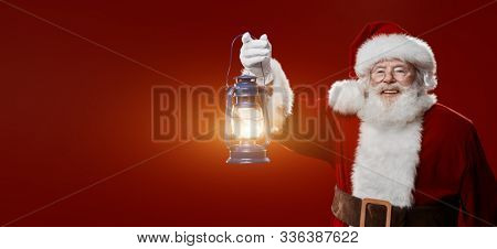Portrait of a jolly Santa with a glowing lantern over red background. Merry Christmas and Happy New Year!