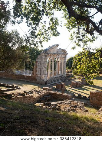 The Restored Temple Of Agonothetes With A Tree Limb And Other Ruins In The Foreground. Photographed