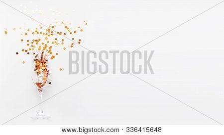 Transparent Wine Glass With Golden Spangles. Festive Copy Space With Crockery On White Background.