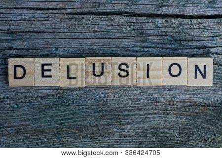 Word Delusion Made From  Wooden Letters Lies On A Gray Background