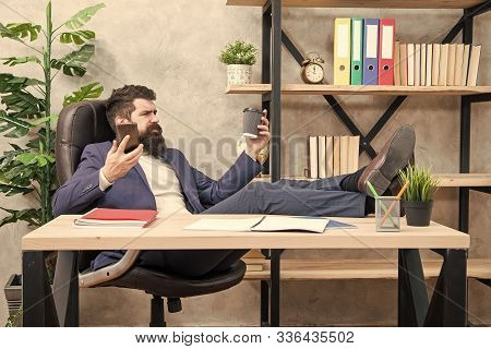 Mobile call. Start day with coffee. Coffee relaxing break. Man bearded businessman hold cup and smartphone. Coffee is pledge of successful negotiations. Caffeine addicted. Boss enjoying energy drink. poster
