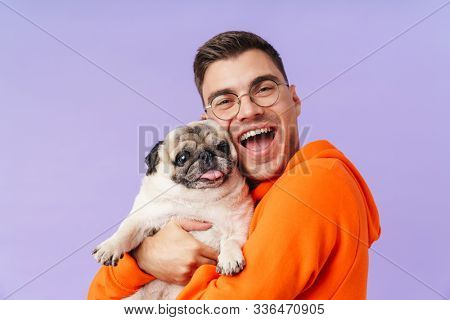 Photo of happy cheery optimistic man posing isolated over purple background holding hugging dog pug.