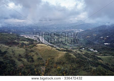 Aerial Photo Of Big Hill With The Trees And Curving Speedroad In Italia In The Clouds On The Backgro