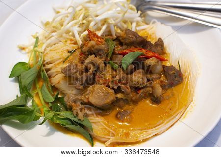 Rice Noodles Topped With Panang Pork Curry And Thai Basil,finger Chilli,bean Sprouts On A White Plat