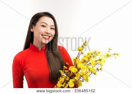 Elegant Asian Woman Holding Peach Flowers While Wearing Ao Dai Over White Background.
