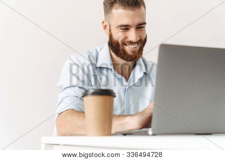 Image of a handsome positive cheery optimistic young businessman isolated posing over white wall background using laptop computer sit at the table.
