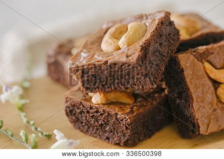 Fresh Baked Dark Chocolate Fudge Brownies. Sweet Brownie Topping With Cashew Nut Stacked On Wood Pla
