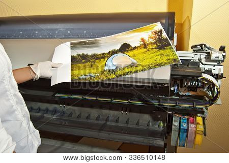 The Girl In A White Shirt Prints A Photo. Woman Looking Through Photo With Magnifier. The Assistant