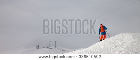 Skier Before Downhill On Snowy Freeride Slope And Overcast Misty Sky At Day With Bad Weather. Caucas