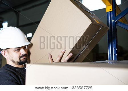 Warehouse Worker With A Hard Hat Holding A Cardboard Box In His Hands. Placing Boxes On A Pile. Safe