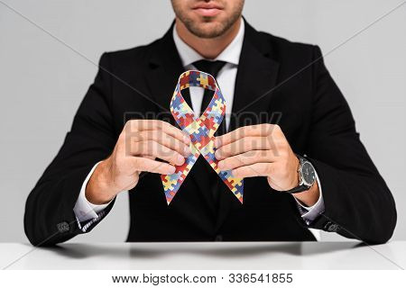 Cropped View Of Businessman In Suit Holding Symbol Of Dyslexia Isolated On Grey