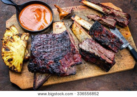 Barbecue smoked sliced hot marinade chuck beef ribs with pineapple and spicy chili sauce as top view sliced on a wooden cutting board