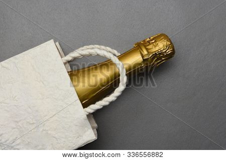 Champagne: Flat Lay Gift Bag with a bottle of sparkling wine on gray tile surface.