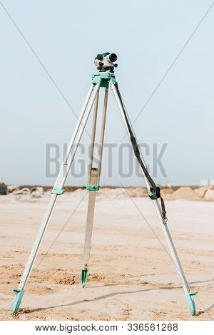 Digital Level For Geodesic Measuring On Dirt Road With Blue Sky At Background
