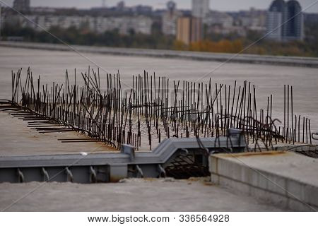 Reinforcing Bars In A Reinforced Concrete Structure Of A Bridge Under Construction Against The Backg