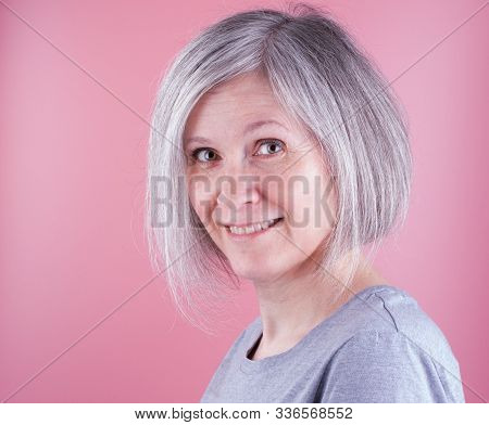 Woman In The Early Fifties With Gray Hair, Pink Background
