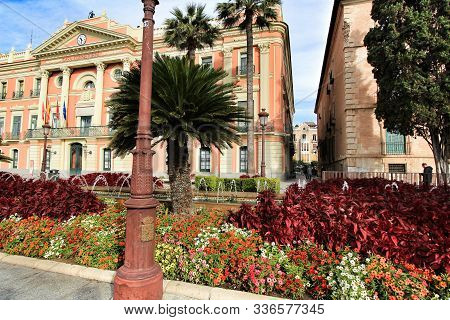Murcia, Spain- November 16, 2019: Beautiful And Antique City Hall Facade And Colorful Outdoor Garden