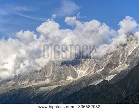 Dense Cumulus Clouds Covered The Peaks Of The Alps. There Is Snow In The Mountains. The Slopes Of Th