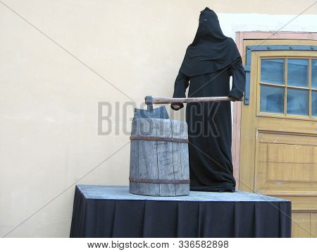 The Grimmed Executioner Of The Death Penalty In Black Costume And Mask With A Huge Sharp Ax On A Sca