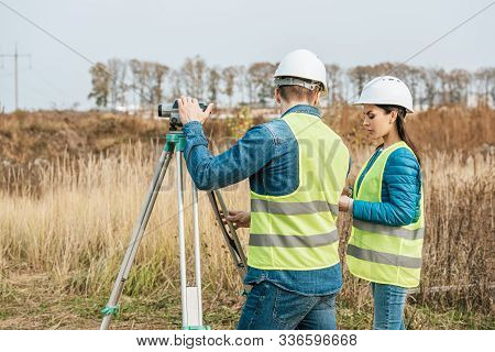 Surveyors Working With Digital Level In Field
