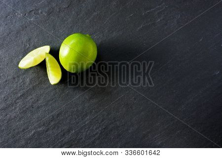 Wedges Of Lime Next To A Whole Lime Ready To Make Cocktails On A Black Slate Background; Copy Space
