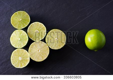 A Triangle Of Lime Halves Point To A Whole Lime On A Background Of Black Slate