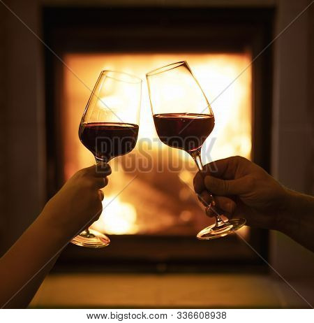 Two Glasses Of Wine On The Background Of The Fireplace, A Loving Couple With Glasses Of Wine In Hand