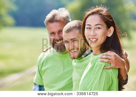 Successful team of environmentalists and activists in green shirt in the park