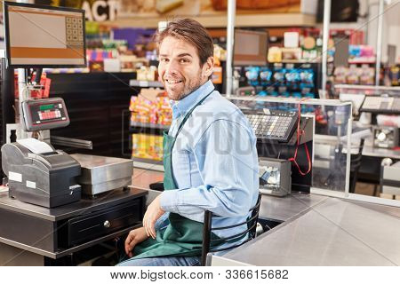 Smiling man as a cashier sits at the cash register in the supermarket