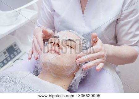 Crop Master Applying White Mask With Brush On Face And Neck Of Young Woman In Towel Lying On Table