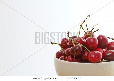 Bowl of bing cherries against white background