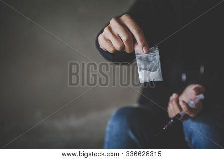 Junkie Man Holding Drug Syringe Injection Heroin To Hand.  Drugs Addiction And Withdrawal Symptoms C