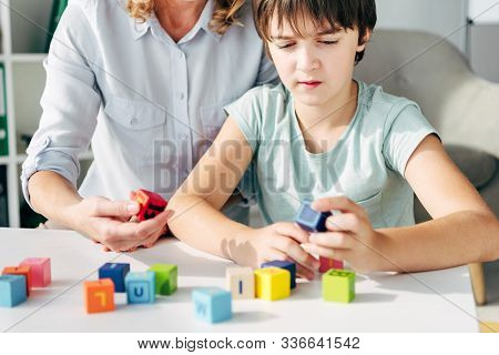 Cropped View Of Child Psychologist And Kid With Dyslexia Playing With Building Blocks