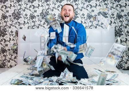 Bearded Man In A Blue Shirt Enjoys A Lot Of Money On A White Bed, A Lot Of Money Flies Around A Man