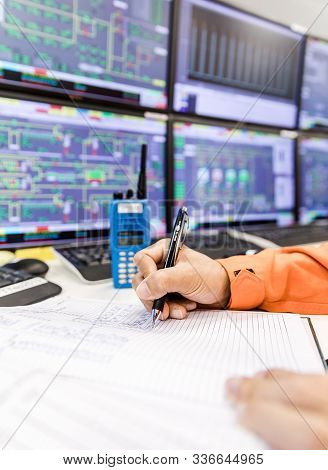 Female Hands With Pen Writing On Notebook For Report Control Panel In Oil And Gas Process Background