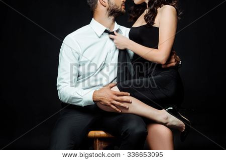 Cropped View Of Bearded Man Sitting On Chair And Touching Sexy Woman In Dress Isolated On Black