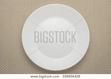 Empty White Plate On Woven Napkin. Clean Plate On Light Brown Tablecloth. Unused Dishes.