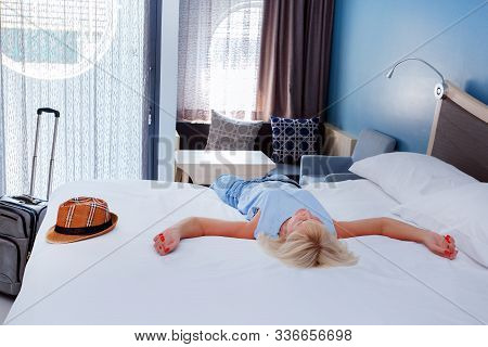 Woman Lying In The Bed Of A Hotel Room. Hotel Guest Relaxing On The Bed In Their Room.