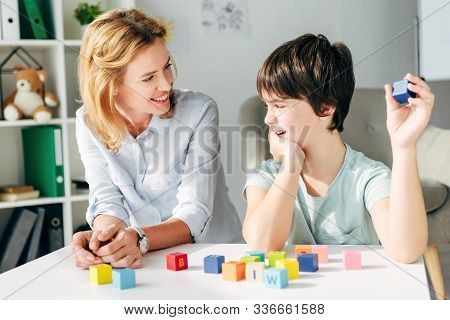 Smiling Child Psychologist Looking At Kid With Dyslexia And Sitting At Table With Building Blocks