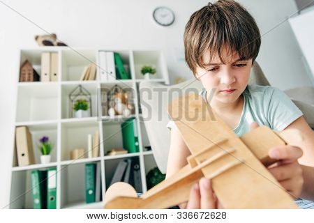 Cute Kid With Dyslexia Playing With Wooden Plane
