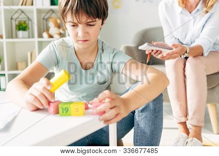 Kid With Dyslexia Playing With Building Blocks And Sitting At Table