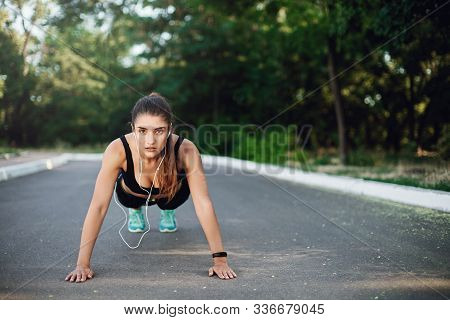 Alluring Determined Young Sporty Woman In Activewear Standing In Plank Concrete Road In Park, Perfor