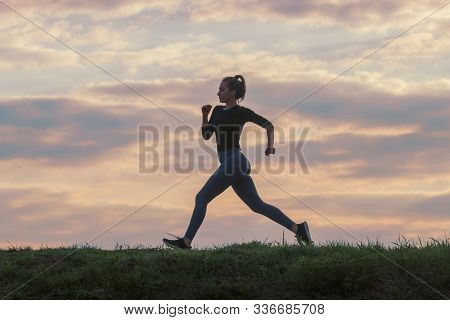 Running Woman Morning Workout. Female Runner. Jogging During Sunrise. Workout In A Park. Sporty Youn