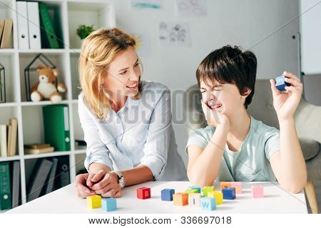Smiling Child Psychologist And Kid With Dyslexia Playing With Building Blocks